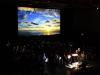 01 \'Clouds\' - gespielt von dem großen Blasorchester unter Leitung von Sonja Unglaub (Bild im Bild v.D.Reichelt)